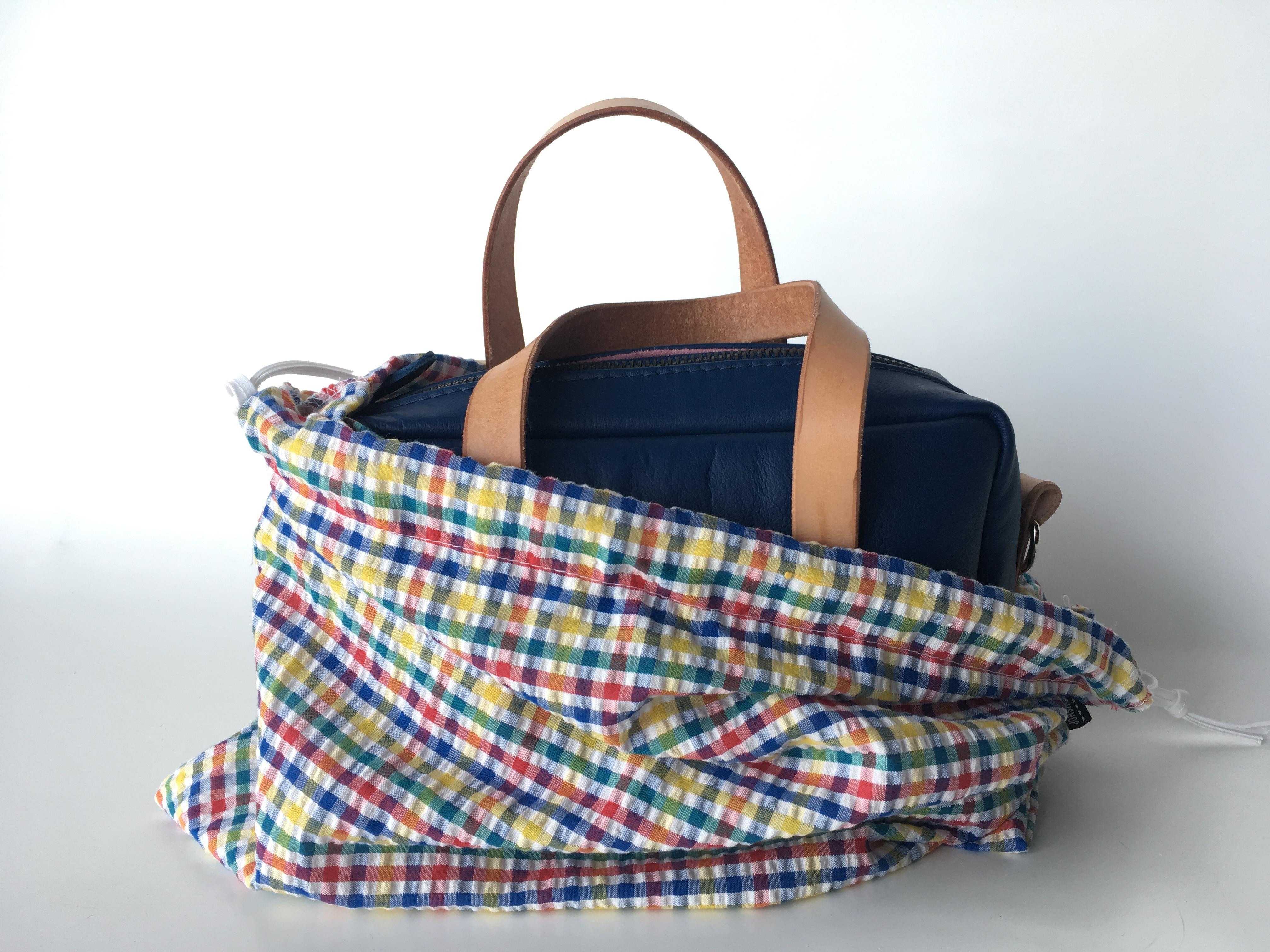 Blue Leather Mini Duffel bag in protective gingham drawstring bag